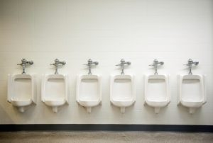A row of six urinals await customers.